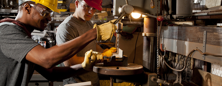 Young adult mechanics in small business repair, workshop. Drill press.